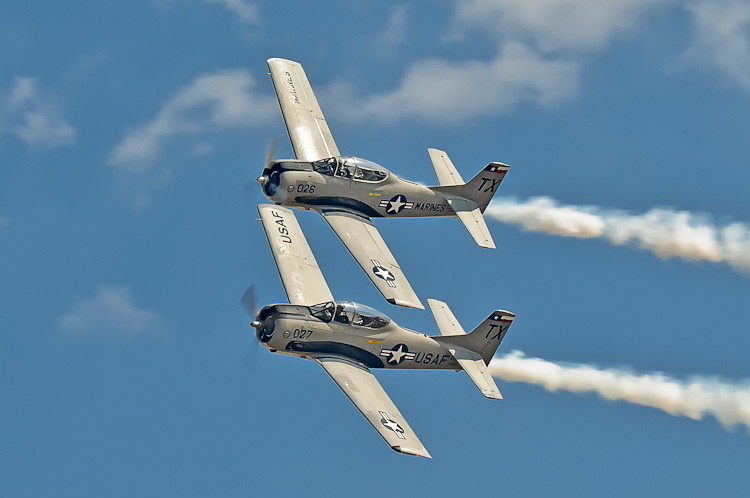 The Trojan Phlyers own and operate two T-28B aircraft. Both aircraft have Wright Cyclone R1820-86B nine-cylinder radial engines rated at 1425 horsepower. The fully aerobatic aircraft can takeoff in less than 800 feet of runway, climb to 10,000 feet in less than 90 seconds, race level above 335 MPH, and dive faster than 380 MPH. In fact, the T28 can outperform most World War II fighters at low altitude.