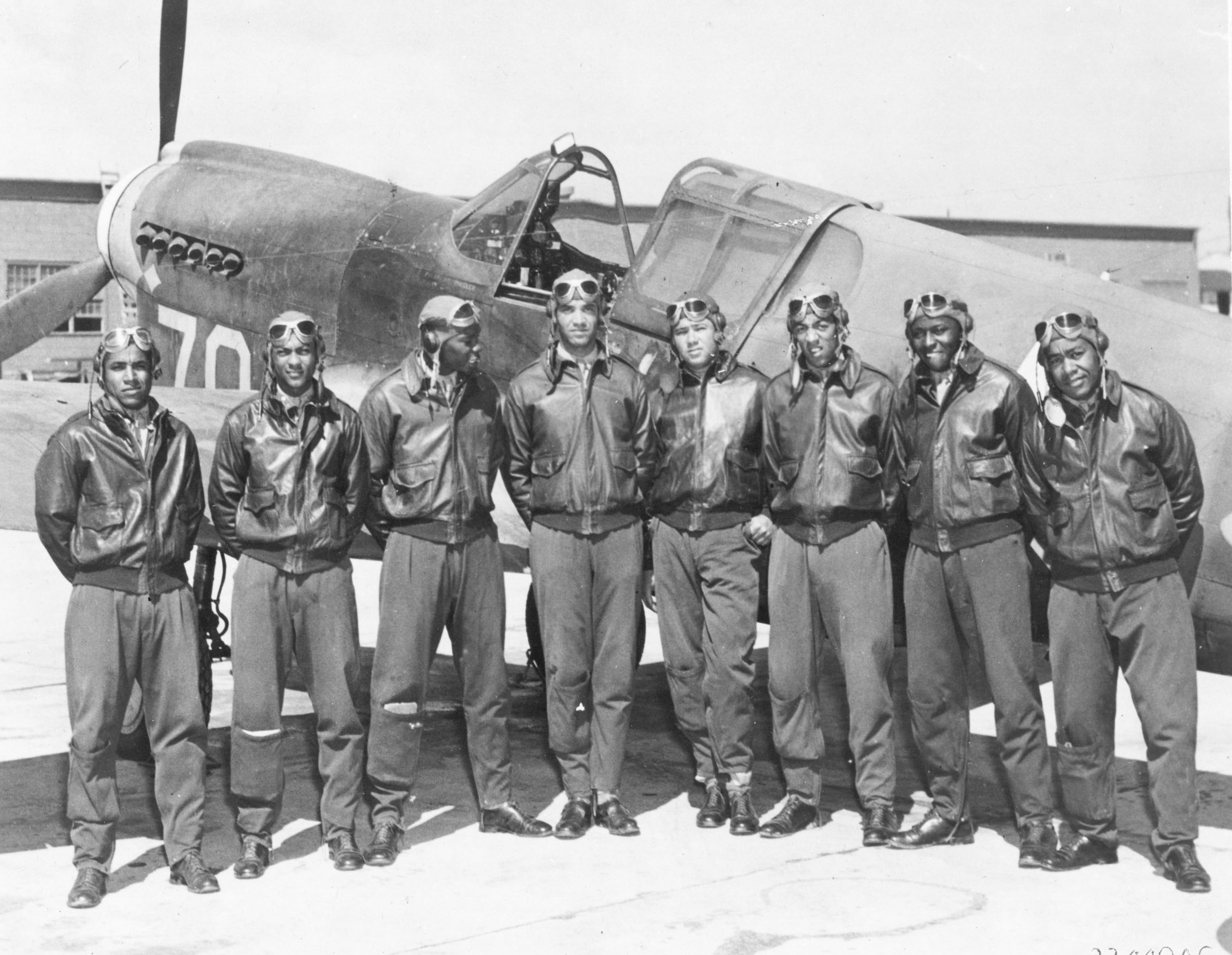 Eight Tuskegee Airmen in front of a P-40. ( Image via Wikipedia)