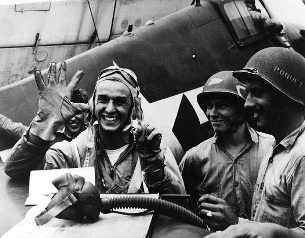 Alex Vraciu holding up five fingers and a thumb, representing the six Japanese dive bombers he had just shot down during battle on June 19th, 1944. (US Navy photo)