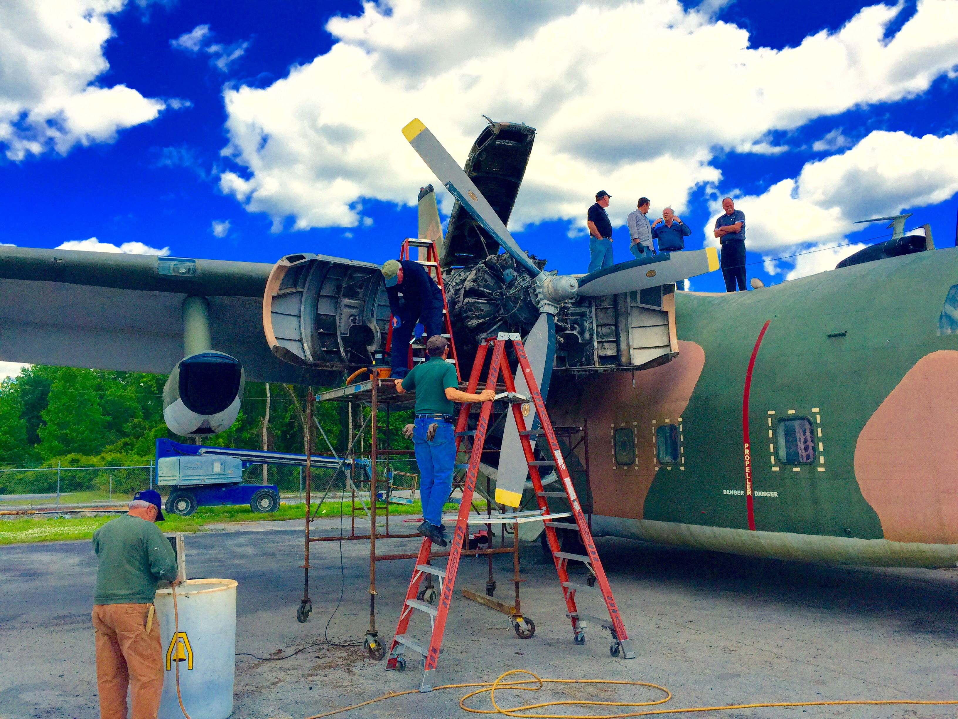 The crew from Warriors & Warbirds working on their C-123K Provider, Ponderous Polly, in April during a trip from their home base in Monroe to New Bern, North Carolina (where Polly is currently stuck). (photo by Joseph Atkins)
