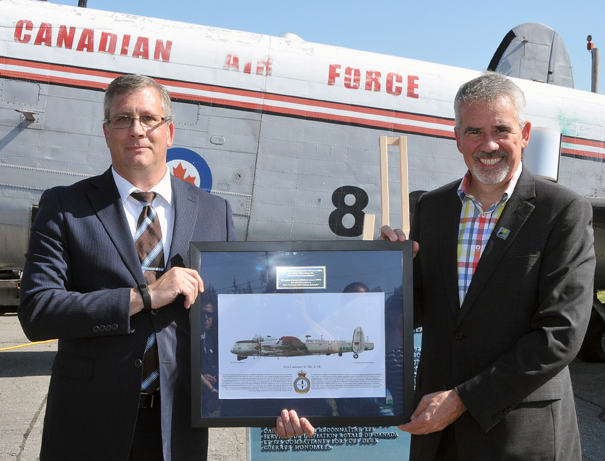 The curator of the National Air Force Museum of Canada, Kevin Windsor (left), presents Edmundston mayor Cyrille Simard with an artist's concept of how KB882 will appear following its restoration. (Photo by Warrant Officer Fran Gaudet DND)