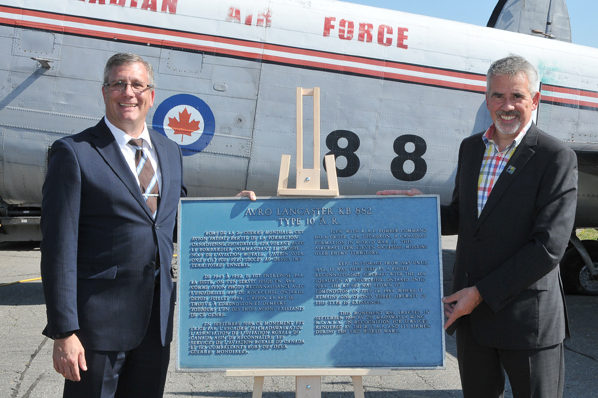 Mayor Cyrille Simard (right) presents Kevin Windsor, curator of the National Air Force Museum of Canada, with the historic plaque that was affixed to a plinth in front of KB882. (Photo by Warrant Officer Fran Gaudet DND)