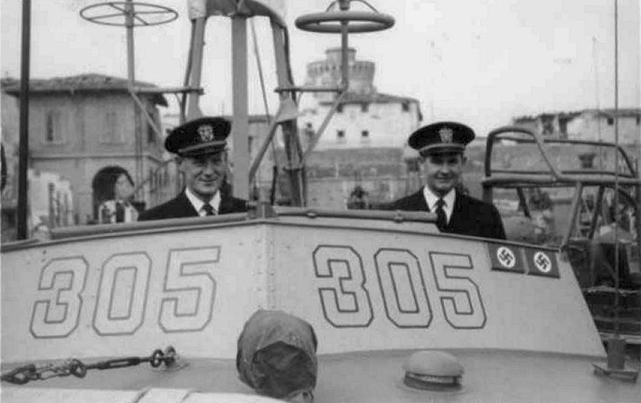 "Ensign Bleeker Morse (left) and Lieutenant Junior Grade Allan Purdy on the bridge of PT-305 in Leghorn (Livorno), Italy, on March 16, 1945. The ""kill plaques"" on the chart house signify the two enemy craft sunk by PT-305 to that date. Gift of Joseph Brannan."