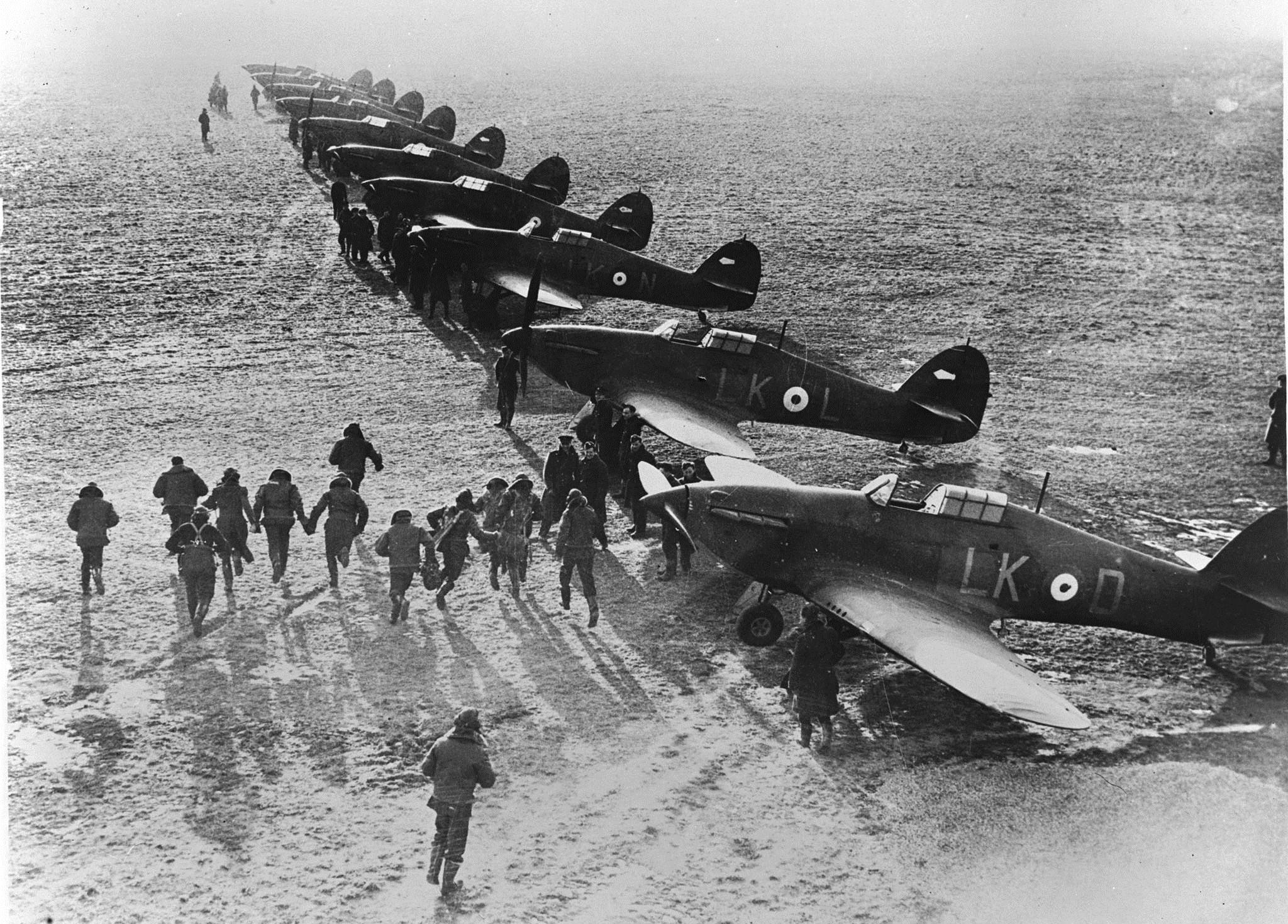 Pilots scramble for their Hawker Hurricane fighters at an airfield in England to tackle the Luftwaffe during the Battle of Britain. (photo via RCAF)