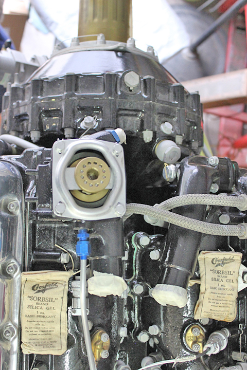 The forward section of a Merlin engine showing two of the water necks in position (note the plastic-capped black tubes at the lower section in between the two silica gel packs. (photo via Tom Reilly)